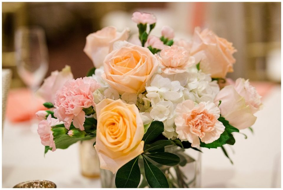 close up of centerpieces with white, pink, and peach flowers