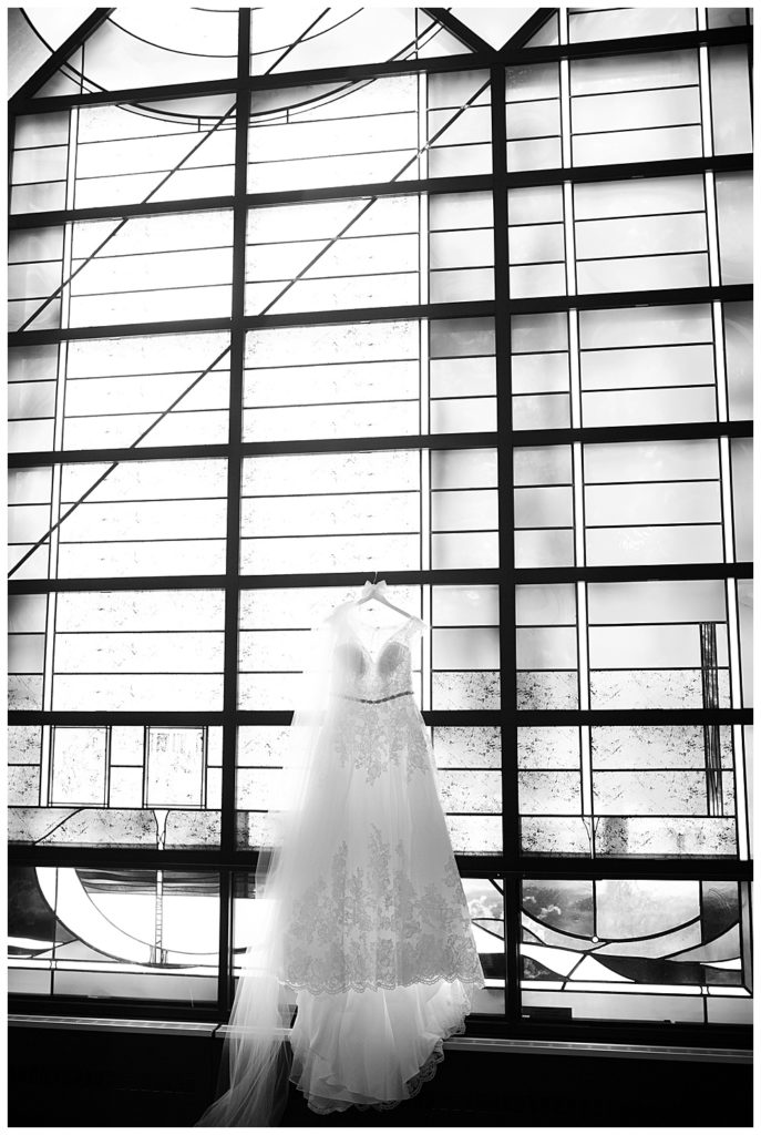 black and white image of wedding dress hanging on stained glass windows