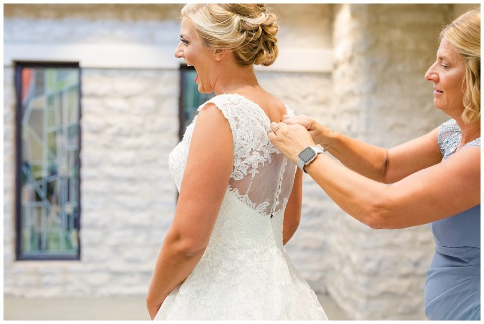 bride laughing with excitement as her wedding dress is buttoned