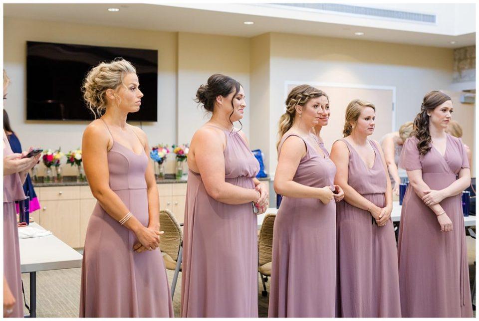 bridesmaids watching bride put on wedding dress