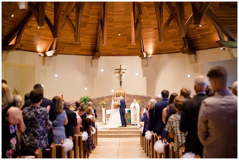 A photograph of a long-range view of the bride and groom standing on the stage as the wedding ceremony ends  by Alayna Parker  - Columbus OH wedding photographers