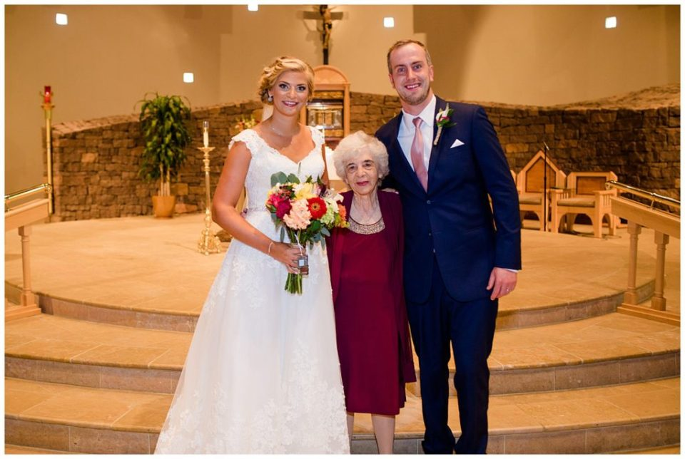 An image of the bride and groom standing with the bride's grandmother after the wedding at the St Andrew church in Columbus by Alayna Parker  -   wedding photographer in Columbus