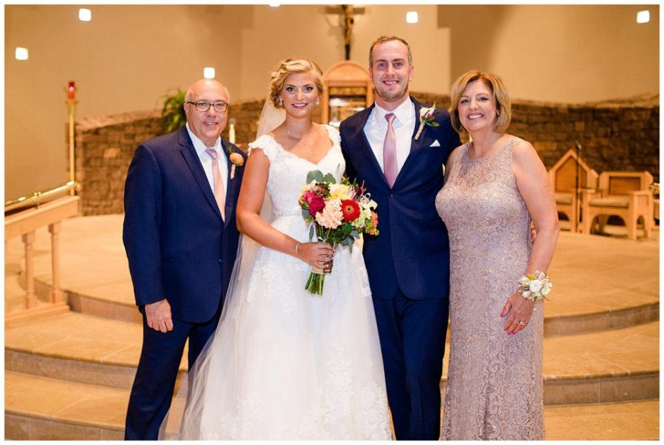 A picture of the bride and groom standing with the groom's mother and stepfather, smiling after the wedding ceremony  by Alayna Parker Photography  -   wedding photographers in Columbus Ohio