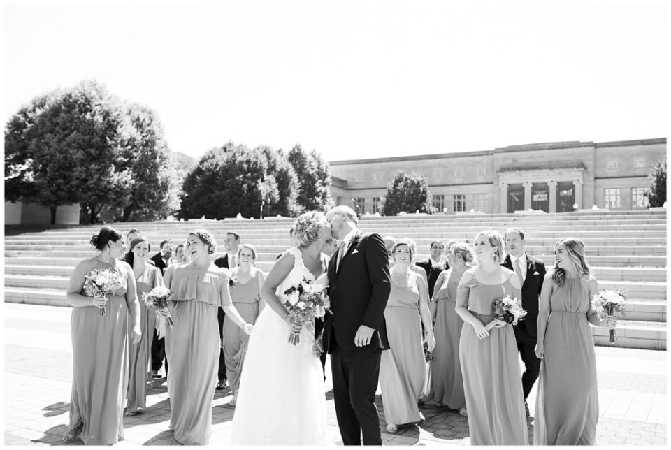 An image in black and white of the wedding party relaxed and visiting while the bride and groom kiss at COSI in Columbus by Alayna Parker Photography  - Columbus Ohio wedding photographers
