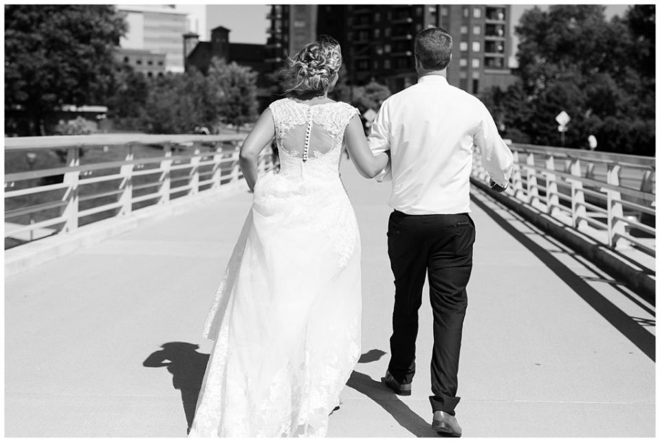 A photograph in black and white of the bride and groom from behind, walking together outside after the wedding at the Washington Street Bridge in Columbus Ohio by Alayna Parker Photography  -   wedding photographers in Columbus Ohio