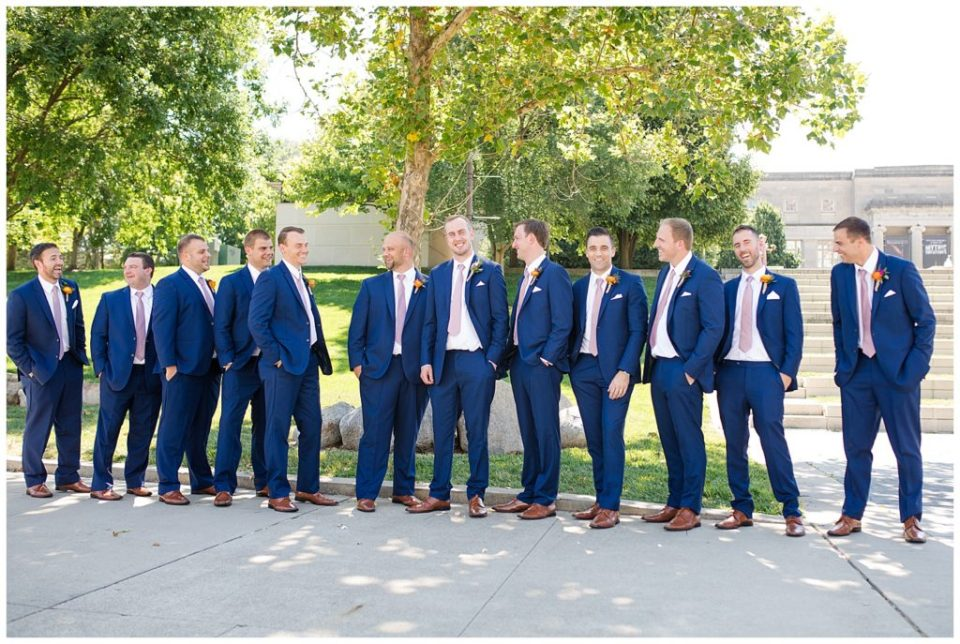 groom and groomsmen laughing in front of steps at cosi