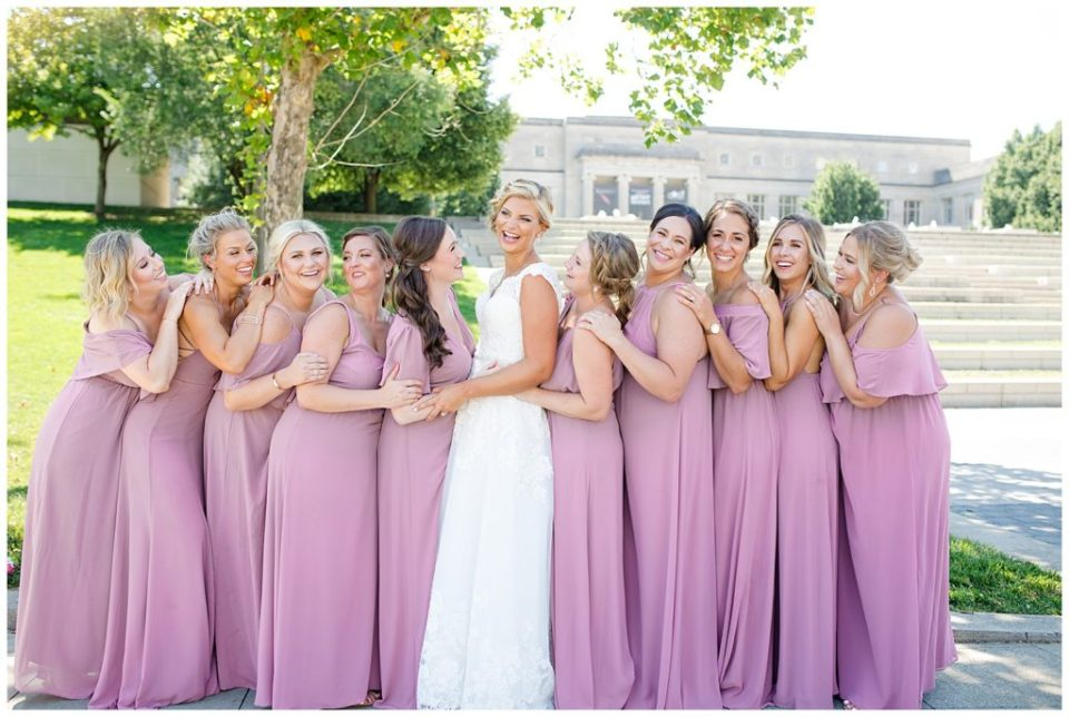 bride and bridesmaids laughing in front of steps at cosi