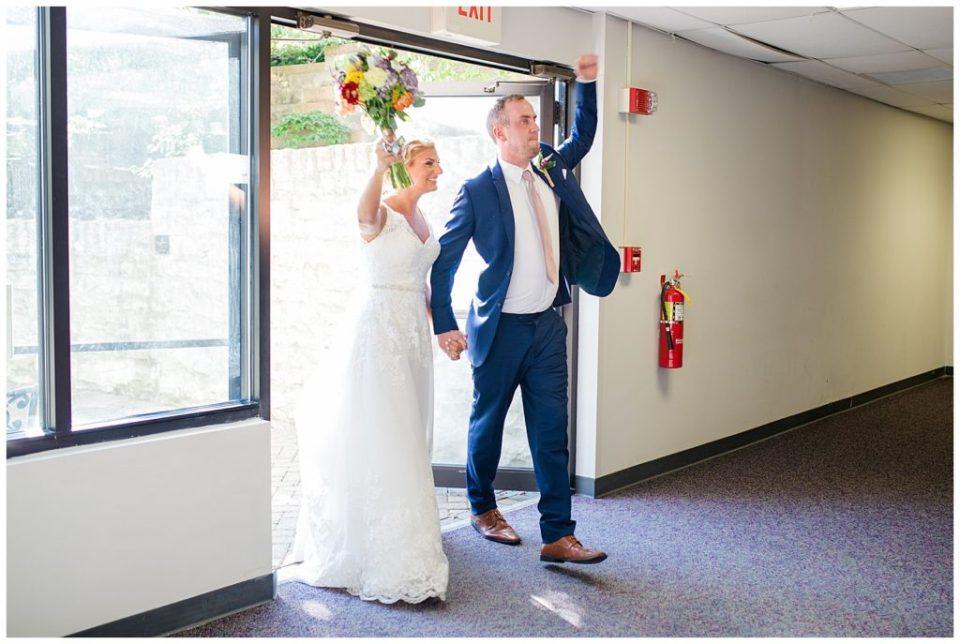 bride and groom cheering as they walk into reception