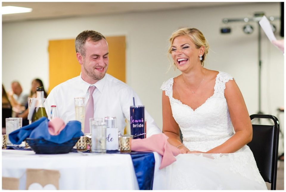 bride and groom laughing during maid of honor's speech