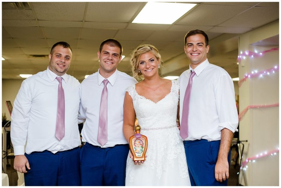 bride and brothers with vintage bottle of whiskey