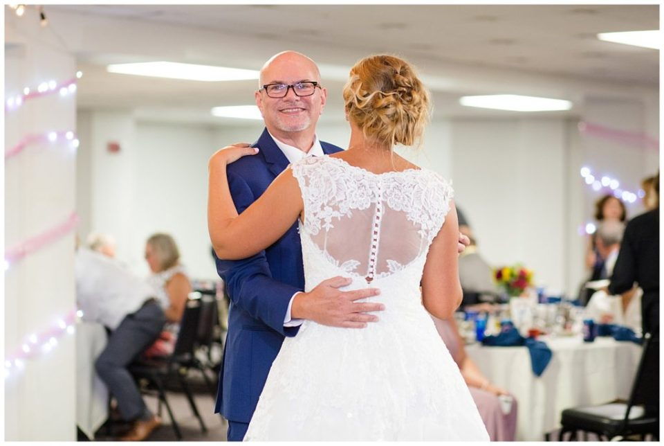 father smiling as he dances with bride