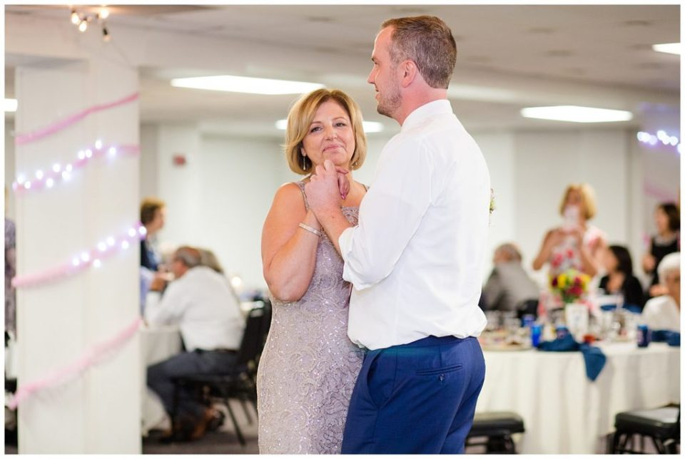 mother smiling as she dances with groom