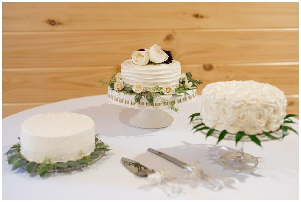A photograph of the wedding cakes arranged on a beautiful table at the wedding reception at the Cedar Grove Lodge venue in Hocking Hills, Ohio by Columbus OH wedding photographer, Alayna Parker Photography