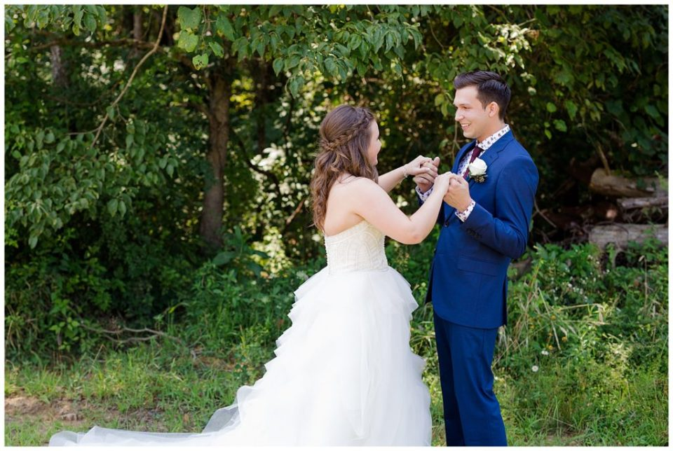 A picture of the bride and groom's first look at each other before the wedding ceremony at the Cedar Grove Lodge wedding venue by Columbus  wedding photographer, Alayna Parker Photography