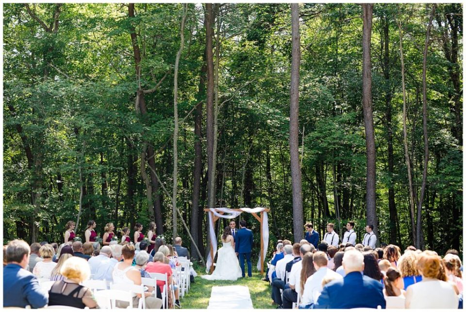 An image of a long-range view of the bride and groom standing with the wedding party during the wedding ceremony in a rustic outdoor setting at the Cedar Grove Lodge wedding venue by Columbus Ohio wedding photographer, Alayna Parker Photography