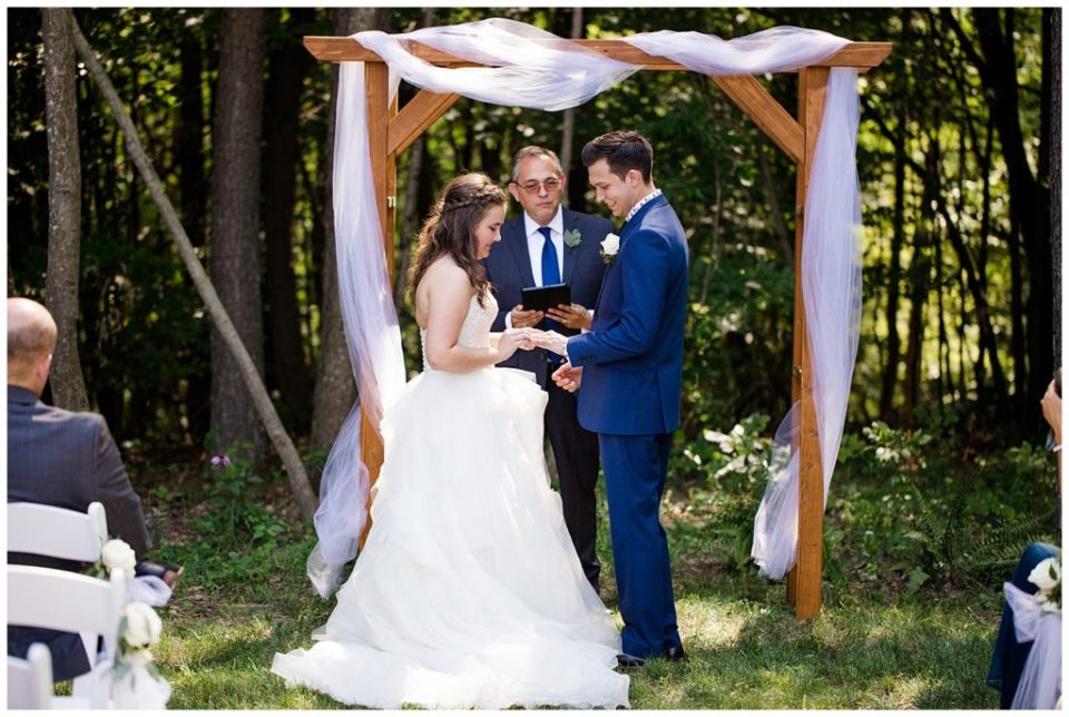 A picture of the bride and groom exchanging rings during their wedding ceremony in a beautiful outdoor setting at the Cedar Grove Lodge wedding venue by Columbus  wedding photographer, Alayna Parker Photography