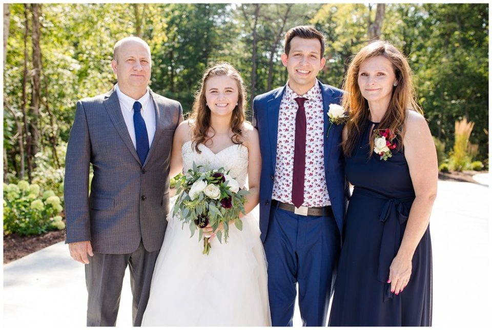 An image of the bride and groom together with their parents following the wedding at the Cedar Grove Lodge wedding venue by Columbus Ohio wedding photographer, Alayna Parker Photography