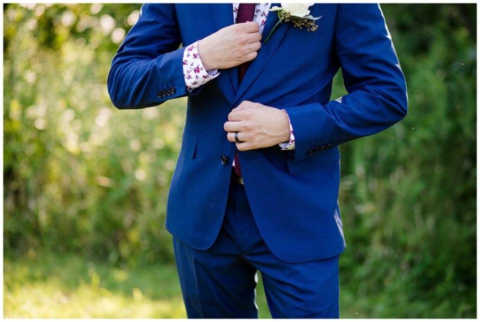 close up of groom fixing tie
