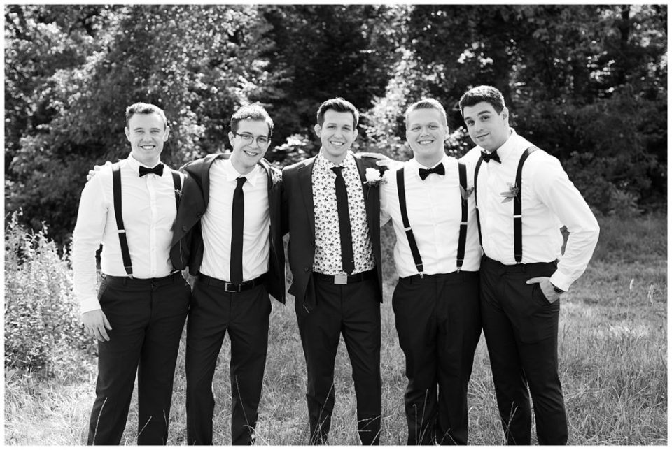 black and white image of groom and groomsmen with arms around each other