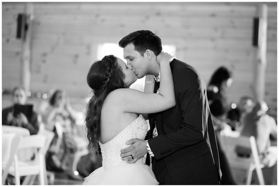 black and white image of bride and groom kissing after first dance