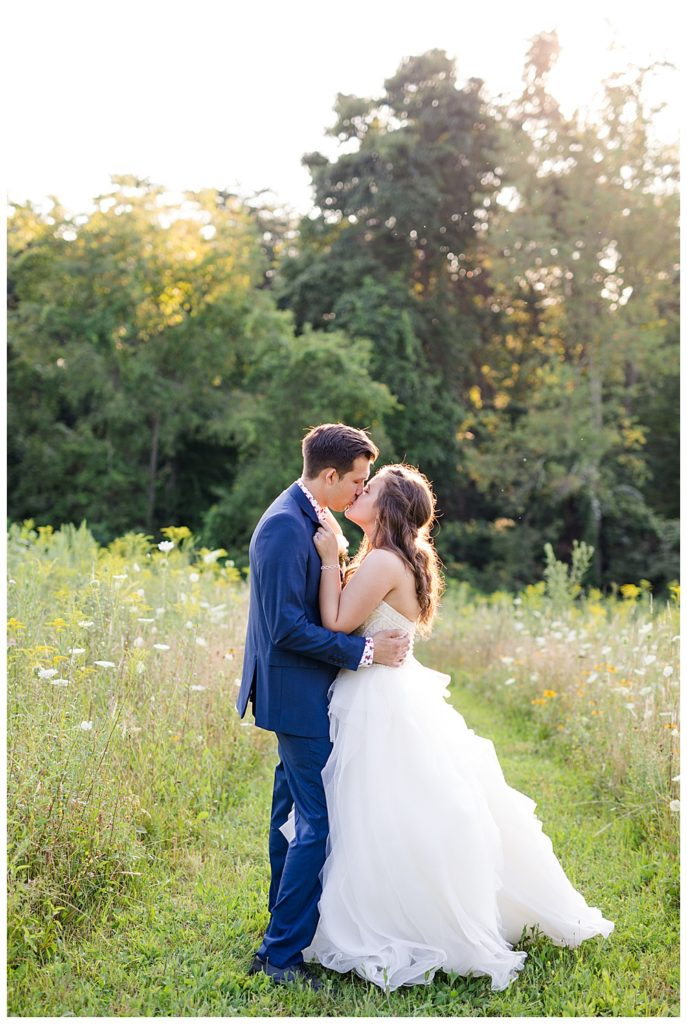 bride and groom kissing in field at golden hour at cedar grove lodge