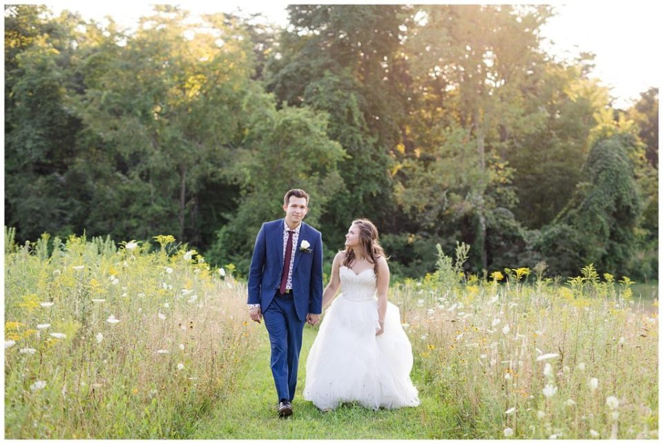 bride and groom walking  in field at golden hour at cedar grove lodge