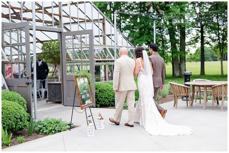 An image of the bride and her father and family member walking the bride into the wedding ceremony hall with her train behind her at the Oak Grove wedding venue by Columbus Ohio wedding photographer, Alayna Parker Photography