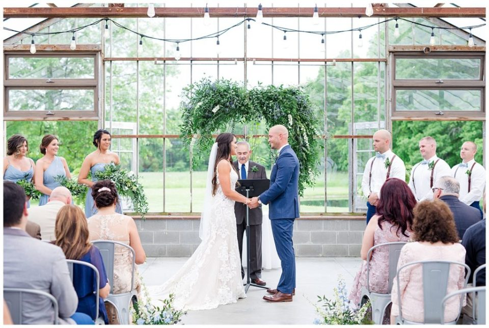 A photograph of the bride and groom holding hands as the officiant repeats the vows at their wedding ceremony at an Jorgensen farms Oak Grove wedding venue by Columbus OH wedding photographer, Alayna Parker Photography