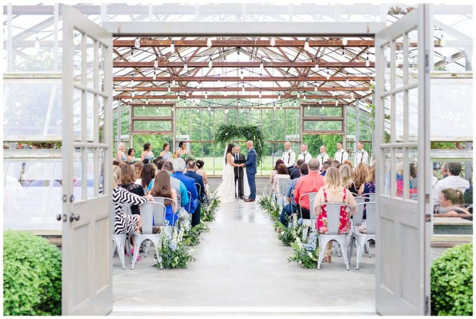A picture of a long-range view of the bride and groom holding hands while repeating their vows at their wedding ceremony at the Oak Grove wedding venue by Columbus  wedding photographer, Alayna Parker Photography