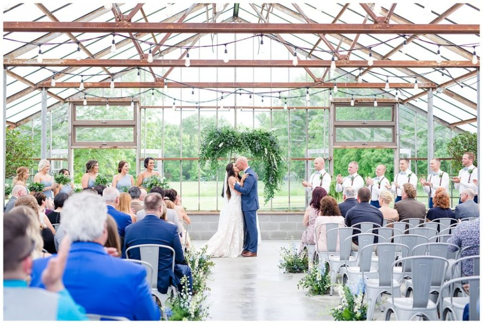 An image of a long-range view of the bride and groom kissing after their vows at their wedding ceremony at the Oak Grove venue in New Albany, Ohio by Columbus Ohio wedding photographer, Alayna Parker Photography