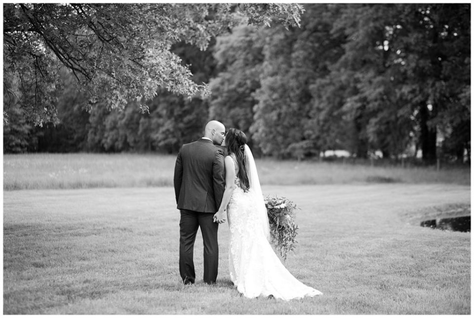 A photograph in black and white of the bride and groom pausing to kiss as they walk outdoors hand and hand at the Oak Grove venue in New Albany, Ohio by Columbus OH wedding photographer, Alayna Parker Photography