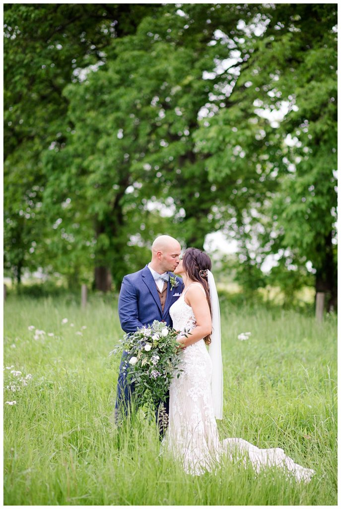 A picture of the bride and groom romantically kissing in a beautiful outdoor setting at the Oak Grove venue in New Albany, Ohio by Columbus  wedding photographer, Alayna Parker Photography