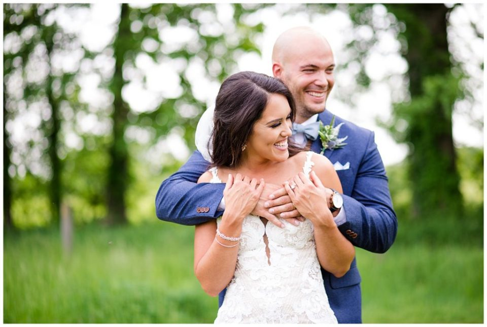 A picture of the groom hugging the bride from behind as they both relax and laugh together at the Oak Grove wedding venue by Columbus  wedding photographer, Alayna Parker Photography
