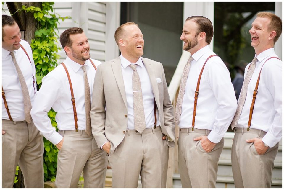 A picture of a groom and his groomsmen standing together, laughing and relaxing before the wedding at Jorgensen Farms wedding venue by Alayna Parker  - Columbus  outdoor wedding photographer