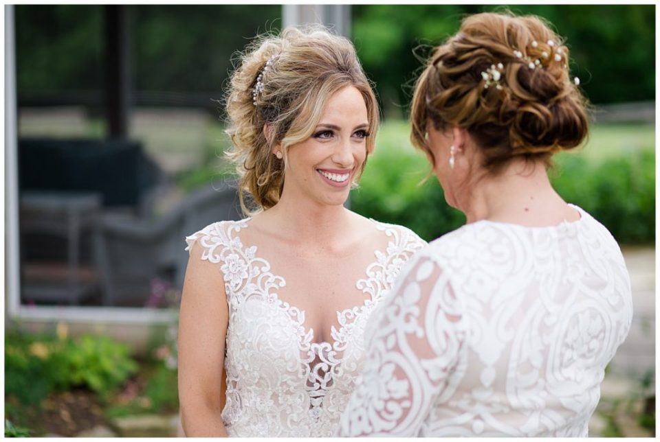 A photograph of a closeup of a beautiful bride smiling with her bridesmaid at Jorgensen Farms wedding venue by Alayna Parker  - Columbus OH rustic wedding photographers