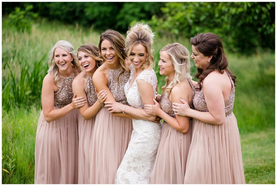 An image of a bride and bridesmaids lined up, relaxing and laughing together at Jorgensen Farms wedding venue by Alayna Parker  - Columbus Ohio wedding photographers