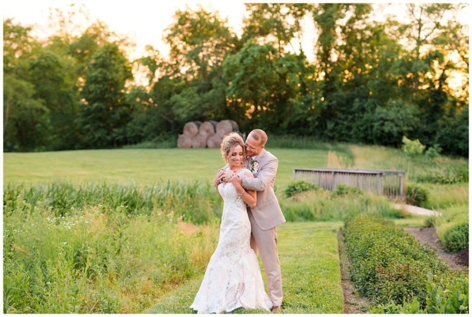 A photograph of a bride and groom embracing romantically in a beautiful outdoor setting at Jorgensen Farms wedding venue by Alayna Parker Photography  - Columbus OH outdoor wedding photography