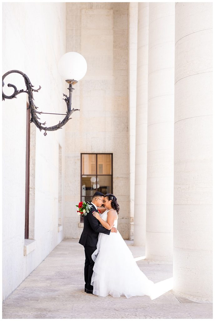 An image of the bride and groom holding each other close, standing in a beautiful colonnade in a long-range shot by Columbus Ohio wedding photography specialist, Alayna Parker Photography