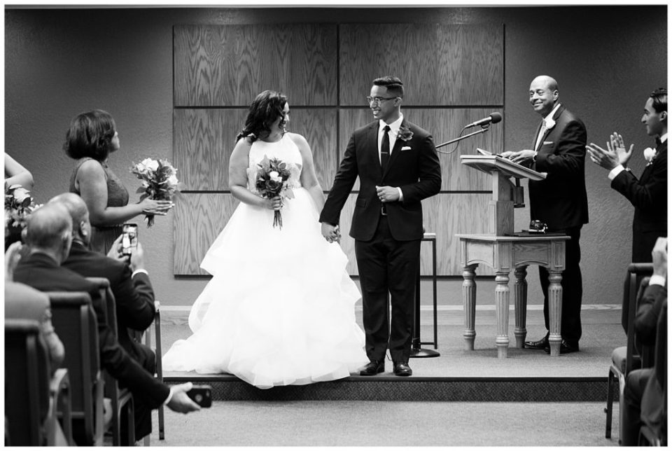 An image of a black and white view of the bride and groom being introduced as a new couple at the wedding ceremony by Columbus Ohio wedding photography specialist, Alayna Parker Photography