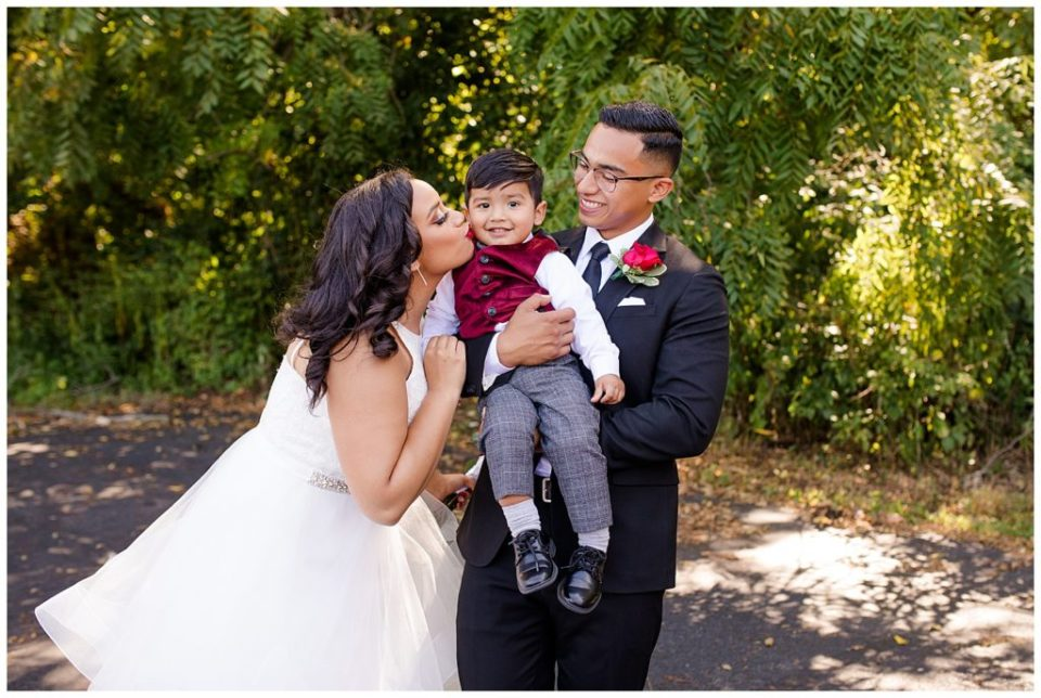 A picture of the bride and groom holding a little family member and sharing a kiss by Columbus  wedding photography specialist, Alayna Parker Photography