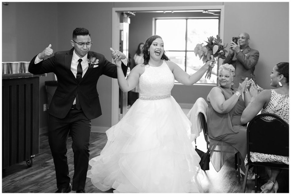 A picture of a black and white view of the bride and groom entering the wedding reception with a lively introduction by Columbus  wedding photography specialist, Alayna Parker Photography