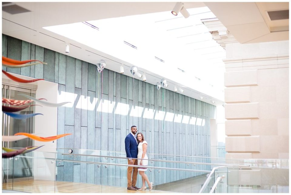 An image of a long-range view of an engaged couple standing close together in an art museum with modern architectural background at the Columbus Museum of Art by Alayna Parker  - Columbus Ohio engagement photography
