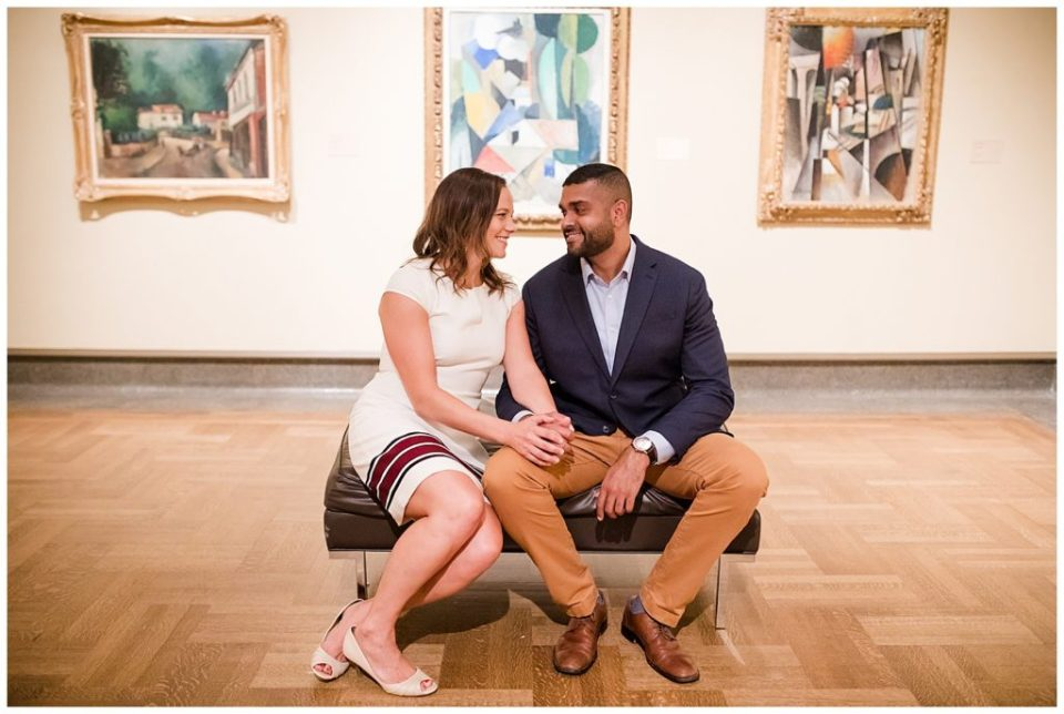 An image of an engaged couple smiling and sitting together on a bench in an art museum at the Columbus Museum of Art by Alayna Parker  - Columbus Ohio engagement photographer
