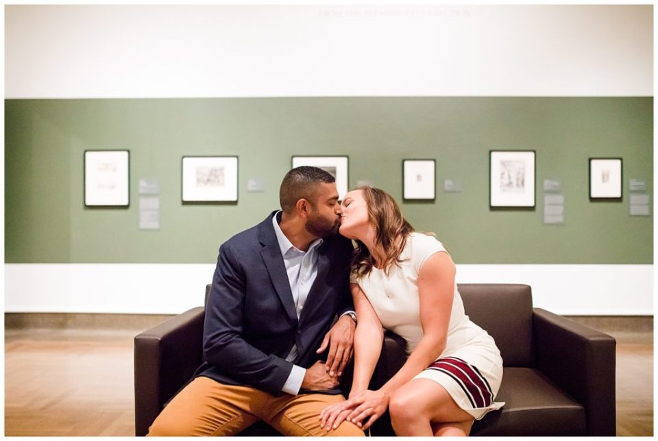 A picture of an engaged couple sitting in an art museum, romantically kissing on a couch at the Columbus Museum of Art by Alayna Parker Photography Columbus  engagement photography