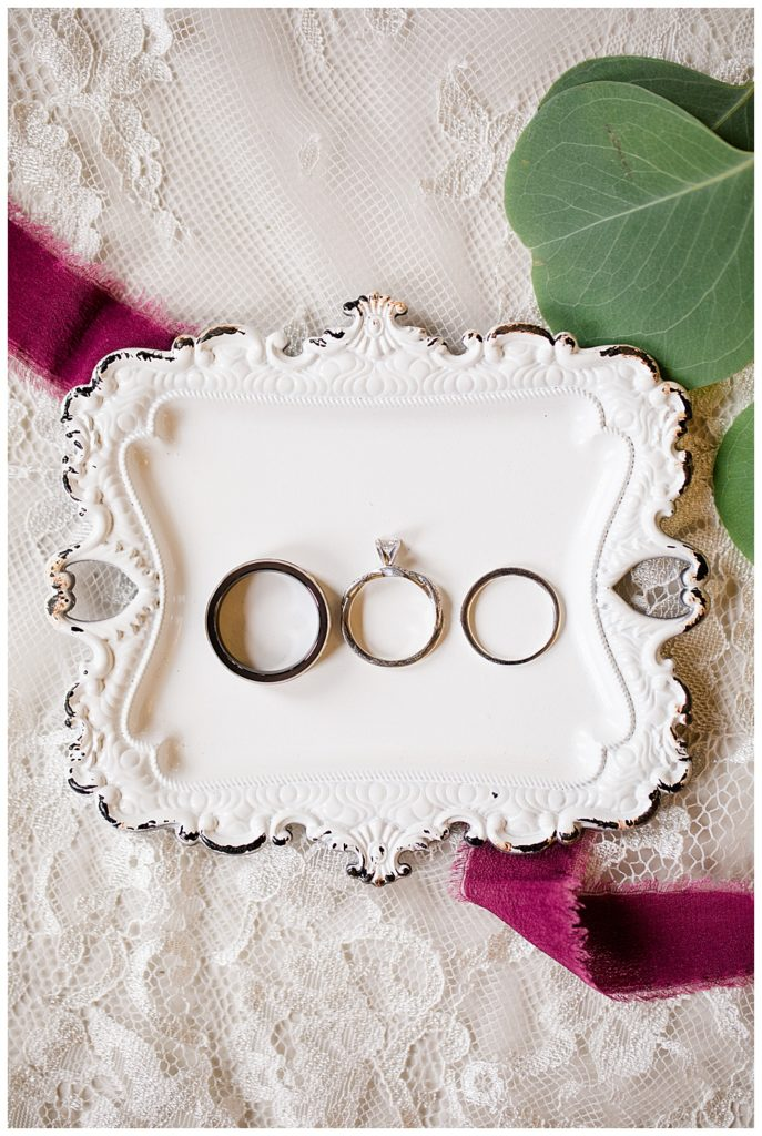 wedding rings sitting on a white antique tray