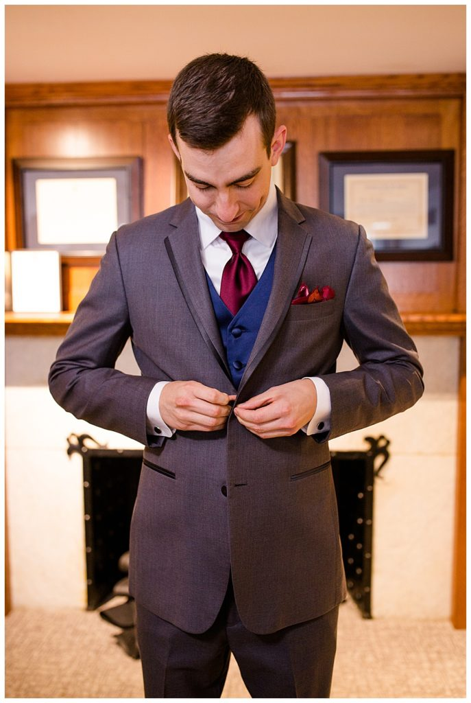 groom buttoning jacket at station 67