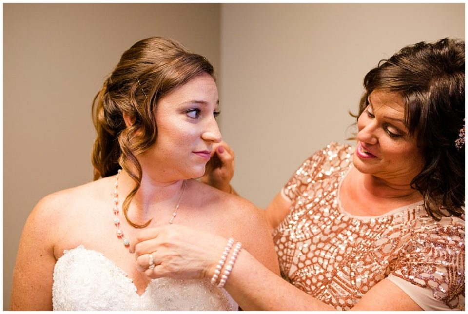 mother helps put necklace on bride