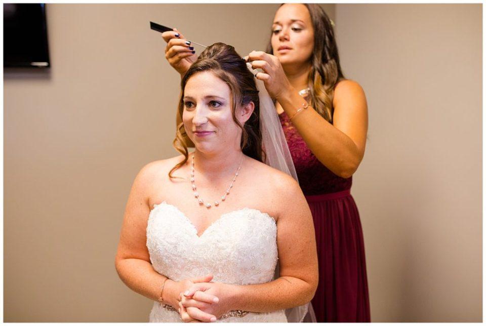 bridesmaid puts veil in brides hair at station 67