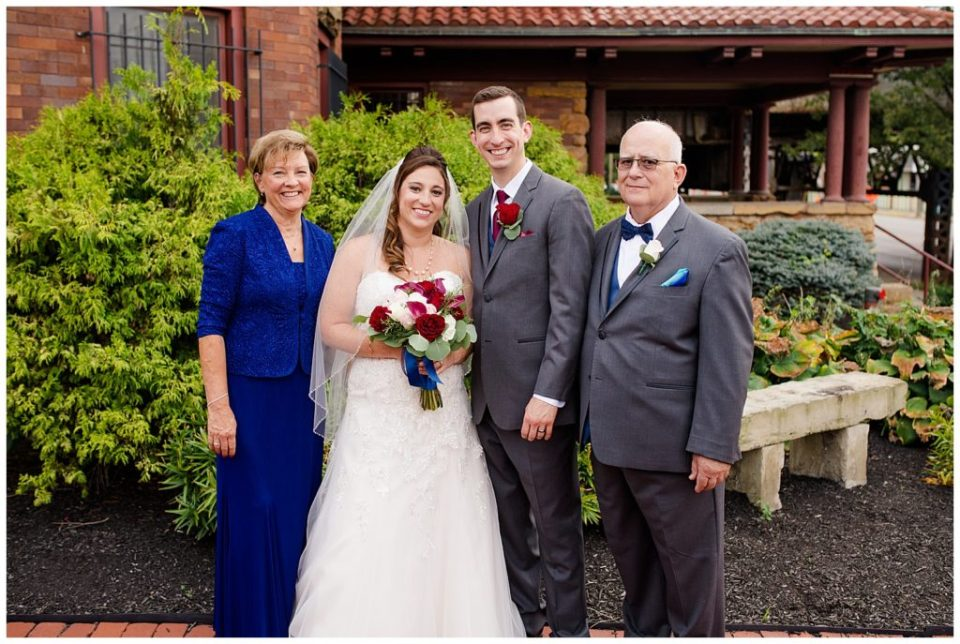 A photograph of the bride and groom standing with the groom's parents after the wedding ceremony at a Station 67 Columbus Ohio wedding by Alayna Parker Photography