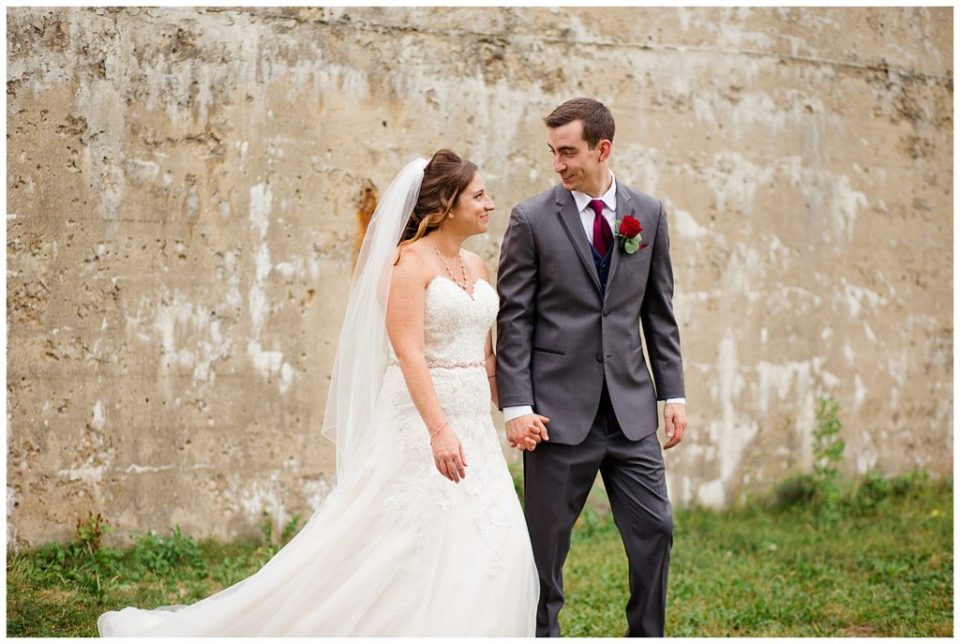 An image of the bride and groom holding hands outdoors, gazing at each other at a Station 67 Columbus  wedding by Alayna Parker Photography